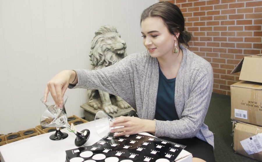 """Ashlin Nicosia, interim development coordinator for University Advancement, shows one of her handmade martini glasses. The glasses, along with other handmade crafts, will be used during """"Chefs Evening."""""""