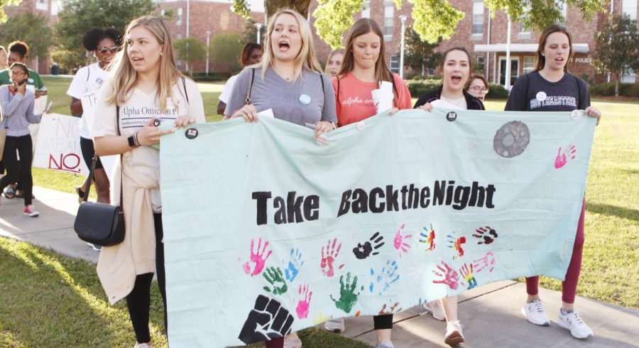 """For """"Take Back the Night Rally,"""" students marched with posters around campus and chanted to raise awareness about sexual assault. Scheduled during Sexual Assault Awareness Month, the march is part of a national campaign to engage students and educate them on the issue."""