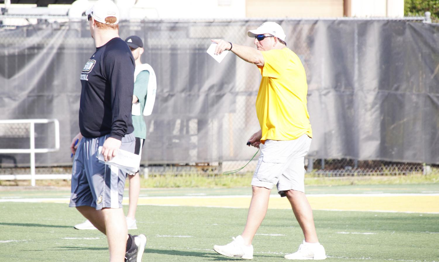 Frank Scelfo, head coach of football, teaches his players various plays at practice. The football team looks to build off of its 4-7 overall record from last season. Scelfo joined the Lions in 2018 following over 30 years of experience coaching the sport.