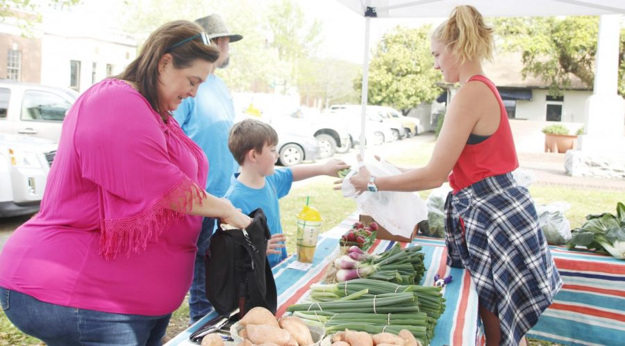 Amanda Fekete sells produce for the Joe Fekete Family Farm at Downtown Development District's weekly farmers market. The farmers market committee handles music and activities for the event every Saturday.
