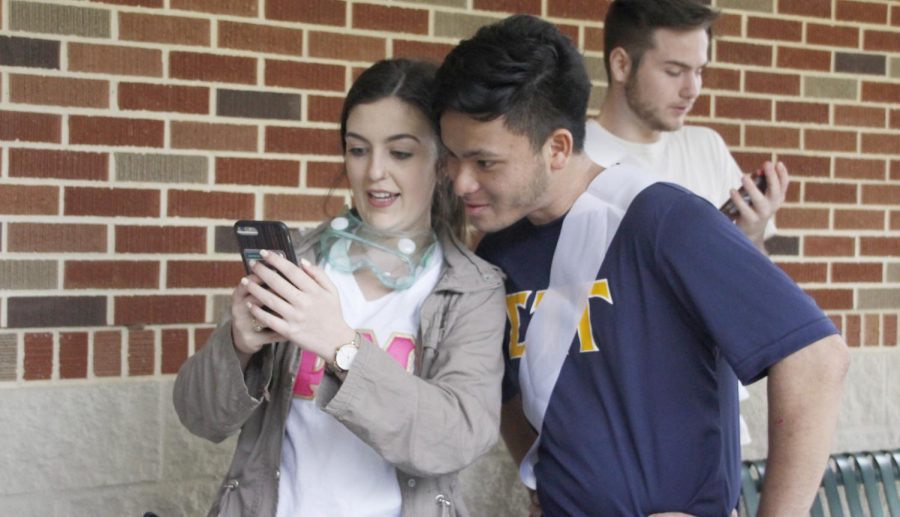 """Breanna Raborn, a member of Phi Mu, and Johnathon Phan, representative on the Greek Court for Sigma Tau Gamma, talk at """"Food Wars."""" Court members can be distinguished at events by a white sash. The Greek Court was introduced for this year's Greek Week, adding to the week's competition."""