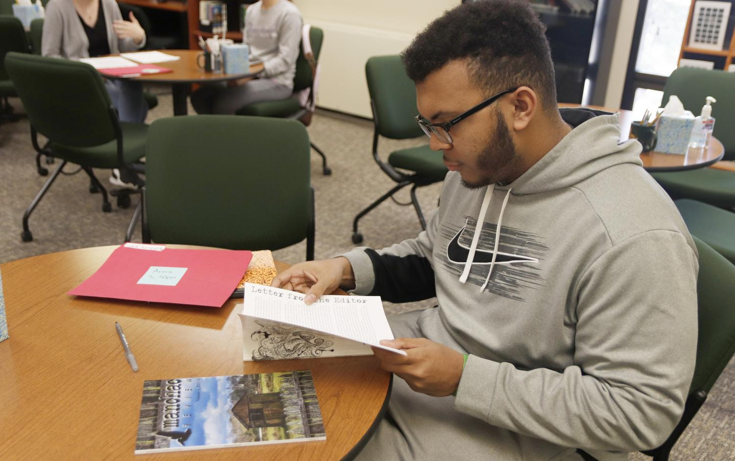 """Roosevelt White, a freshman art major, reads """"The Manchac Review"""" at the Writing Center. The creative magazine is published annually, and students with any major can submit their applications."""