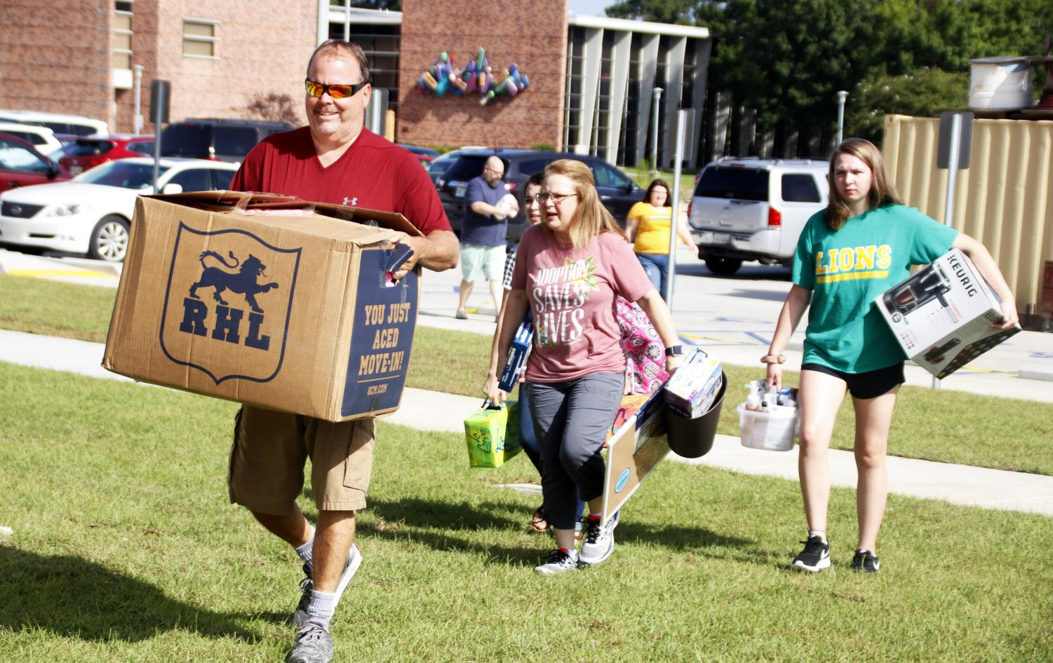 Students and their family carry boxes into the dorms during Move in Mania. Knowing what you do and do not need for college is crucial before going off to live on your own.
