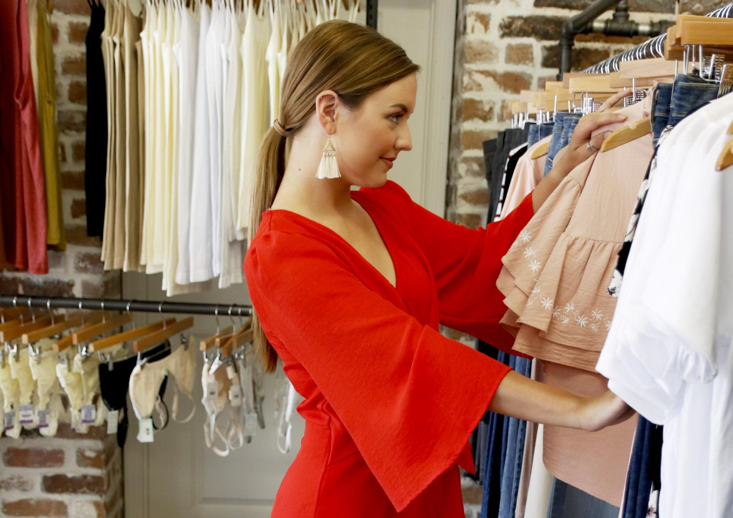 Miss Southeastern Louisiana University models a romper from Imagine Boutique as she looks through their clothing racks. Throughout Hammond are multiple boutiques preparing for tailgate season.