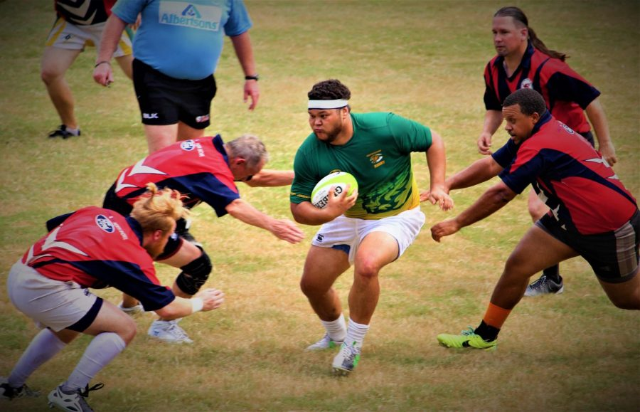 Cody Downs, a junior forward, runs with the ball among four players of the opposing team. The match on Sept. 21 served as a training opportunity for the players on the Rugby Club team.