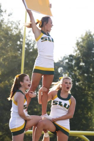 The university cheerleaders enagage crowd during a home game. The cheerleaders practice three times a week and started practicing in June for the fall semester.