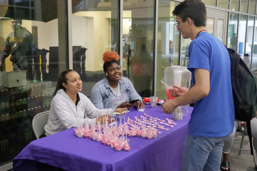 Alexis Novel, vice-president for ELITE Women and Kayla Monlyn, president for ELITE Women sell pink cake pops and lemonade to raise fund and spread awareness about breast cancer.