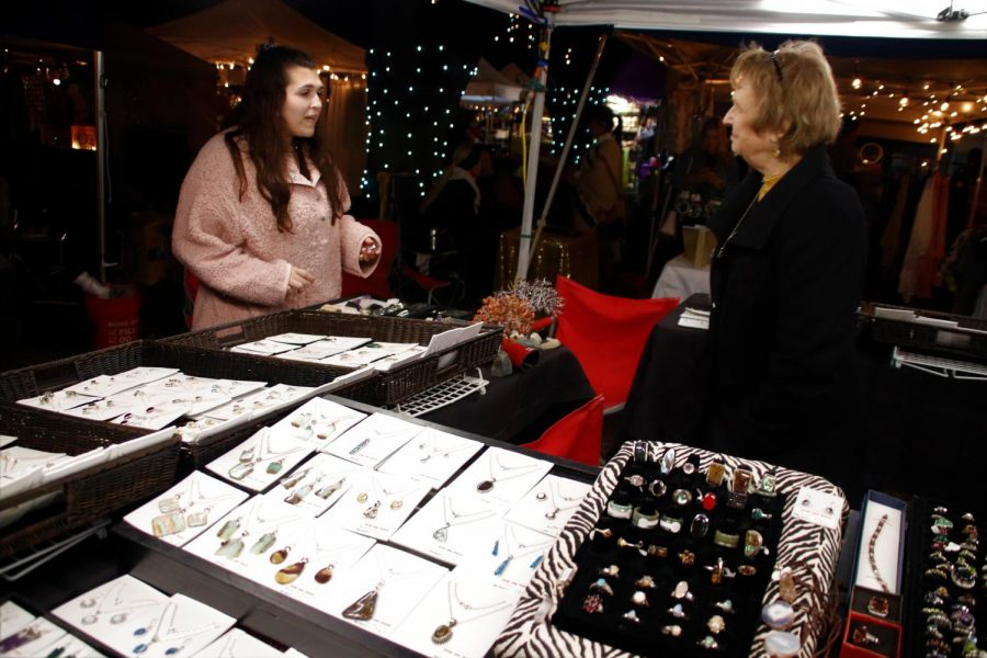 A customer talks with Videt Catania, co-owner of KatanYada. Catania's busniess sells jewelry made from rock that she and her husband collect.