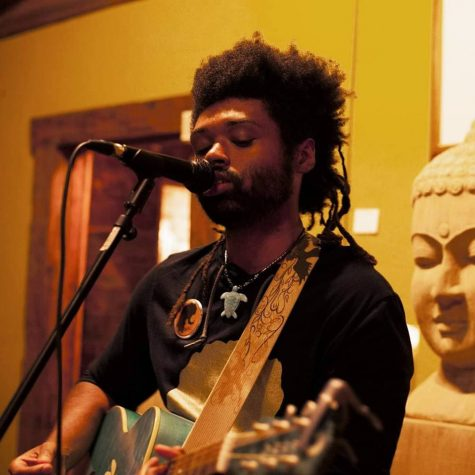 Ameal Cameron performs at a venue. Cameron is an alumnus, singer, songwriter and guitarist.