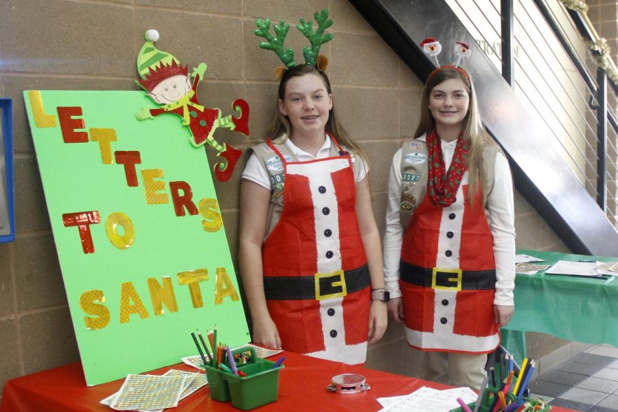 """Vendors at the """"Jolly Jingles Market"""" dress up as Santa's helpers and set up tables for children to draw and color Christmas-themed pictures. The market also hosted live music from multiple elementary schools in the Hammond area."""