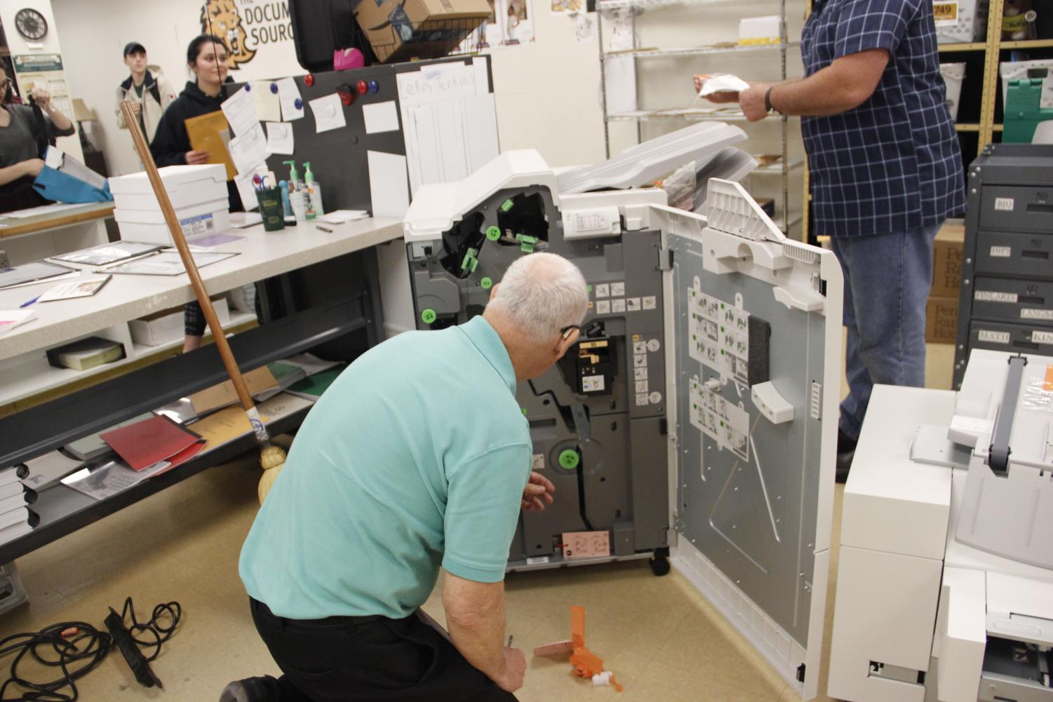 Workers set up the new printing equipment at The Document Source. The office serves students and faculty with their printing and mailing needs.