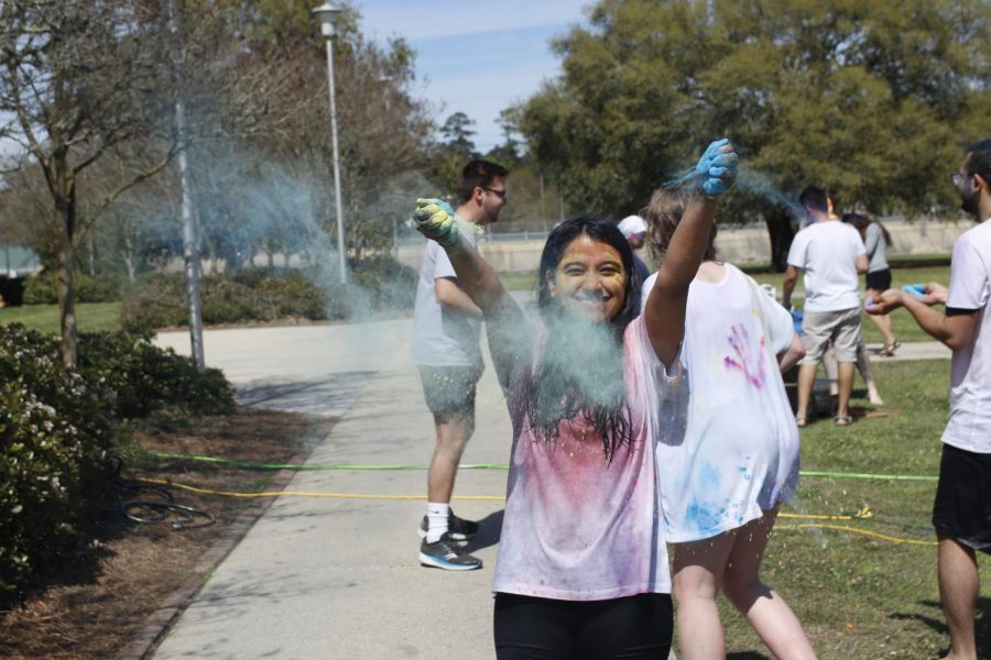 Dipika Ghimire, a junior nursing major, plays with color during Holiday festival organized by the Nepalese Students Association at Southeastern.