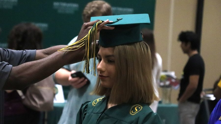 A representative from Candid Campus Pics prepares a student for her cap and gown pictures during Grad Fair. Students could also pick the yearbook and rings during the event.