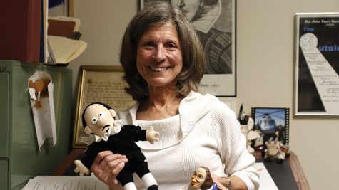 Dr. Joan Faust smiles and poses in her Shakespeare corner, including her Shakespeare-themed doll and rubber duck. Dr. Joan Faust smiles and poses in her Shakespeare corner, including her Shakespeare-themed doll and rubber duck.