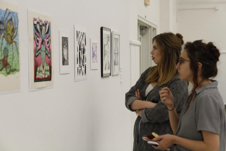 Students examine pieces featured in the 2018 Student Exhibition. This year, the traditional student exhibition will return after a one-year absence.