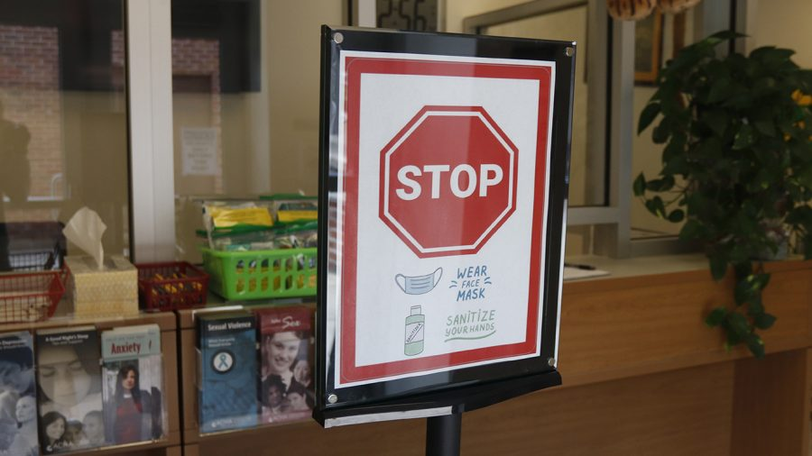 Sign posts in the University Health Center advise students to wear masks and sanitize their hands. Several university stations instruct students to be cautious of their actions to combat the spread of COVID-19.