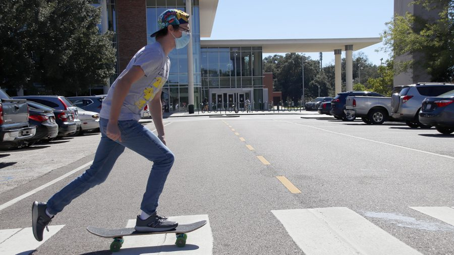 Trevor Tolar skates across the crosswalk in front of Sims Memorial Library. A number of students use various modes of transportation to get around campus.