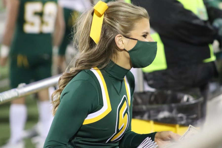 A university cheerleader smiles at fans while she sells programs at the football game in Strawberry Stadium on March 6, 2021. Despite precautions put in place, fans showed their Lion pride with family and friends after 461 days since the last home game.