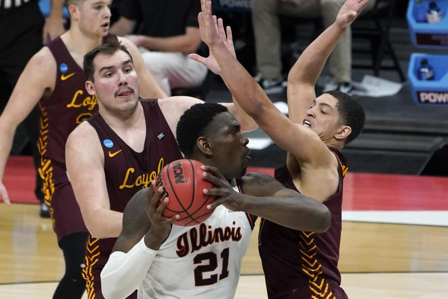 Illinois center Kofi Cockburn (21) is defended by Loyola Chicago center Cameron Krutwig, left, and Lucas Williamson, right, during the first half of a men's college basketball game in the second round of the NCAA tournament at Bankers Life Fieldhouse in Indianapolis, Sunday, March 21, 2021.