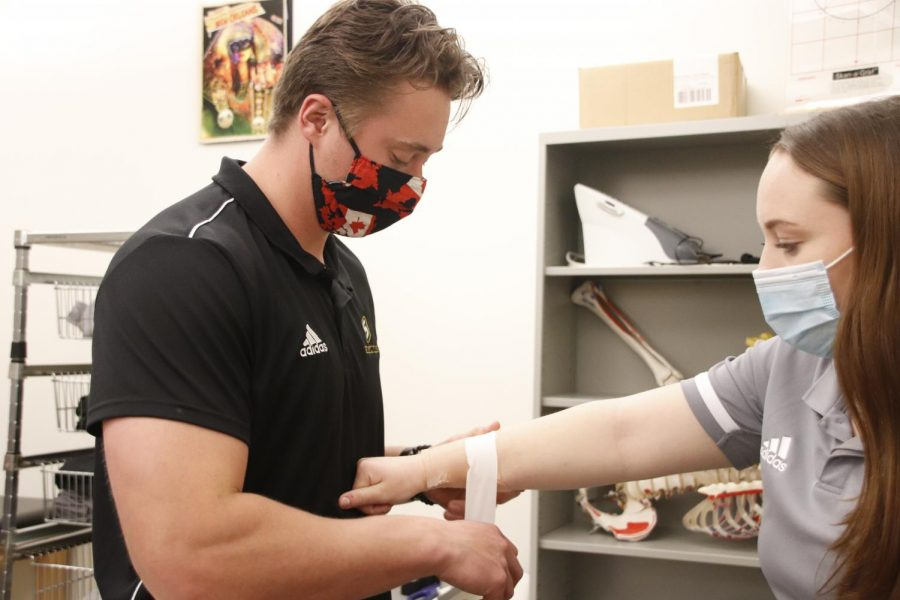 Junior Thomas Nedow wraps senior Rachel Wilkerson's wrist to demonstrate how students have hands-on learning opportunities in Southeastern's athletic training program.