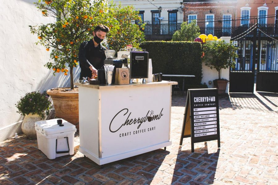 Junior marketing major Noah McLain serves coffee at his pop-up cart. McLain is head of the coffee-catering business that offers coffee brewed form fresh, authentic ingredients.
