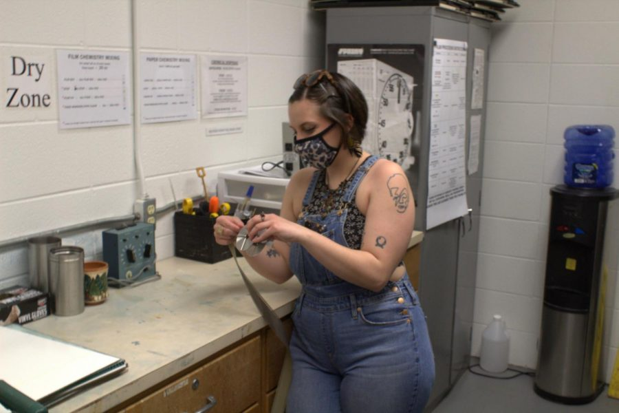 Chloë Bishop, a visual arts major, rolls film from an analog camera into a spool for easy storage.
