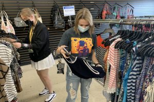 Freshman computer science major Abby Ortego looks through clothes at Goodwill. She is searching for professional clothes so that she can give a speech.
