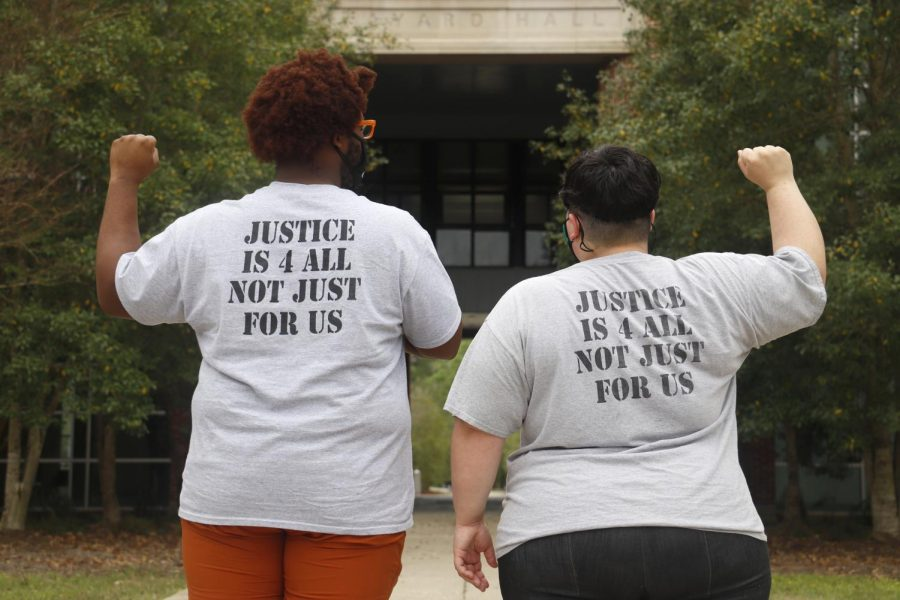 Justice4All's President Michaela Thorpe (right) and Vice President Lynzeryus Railey (left) display their solidarity for social justice advocacy. Both officers are graduate students in the university's applied sociology program. They are wearing T-shirts that were given out at the J4A meeting on March 24.
