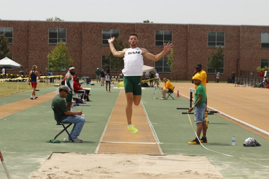 Sophomore Damon Herod leaps off the board at the long jump event during May 1s pre-conference track and field meet.