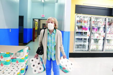 """Maiah Woodring, a senior biological sciences major from Albany, earned a first-place award for this photo in the """"Best News Photo"""" category of the Louisiana Press Association Better Newspaper Competition. The subject of the award-winning photo was a woman wearing a mask gathering items at Walmart on March 16, 2020, in Hammond. Toilet paper became one of the much sought after items as many prepared for an extended """"quarantine"""" at home."""