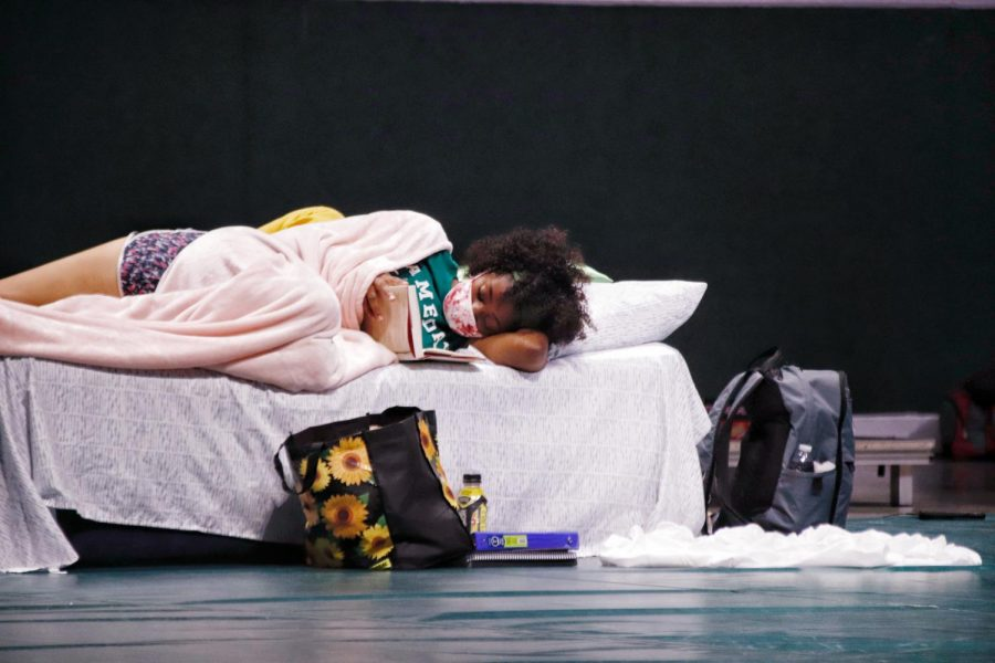 Inside the University Center on Aug. 29, a student evacuee passes time by reading a book, sharing an inflatable air mattress with a fellow student.