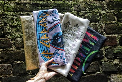 Kayla Morgan shows off some of her band T-shirt clutches. Morgan is a local designer who has an online store called Kay-la Handbags.