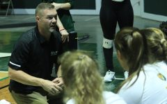 Head Coach Jeremy White speaks with players between sets during Thursdays game against Nicholls State University.